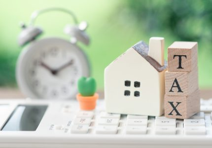 A model house model is placed on wood word TAX . as background property real estate concept with copy space for your text or design.